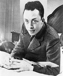 Albert_Camus,_gagnant_de_prix_Nobel,_portrait_en_buste,_posé_au_bureau,_faisant_face_à_gauche,_cigarette_de_tabagisme.jpg